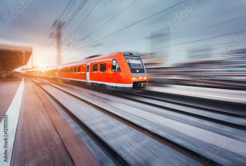 Piękna stacja kolejowa z nowożytną wysoką prędkość czerwoną kolejką z ruch plamy skutkiem przy kolorowym zmierzchem. Kolejowa z promieni słonecznych. Vintage tonowanie. Podróżować. Pociąg