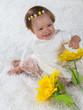 Quadro Маленькая девочка смеется сидя на белом ковре