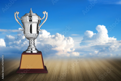 silver trophies on wood table with blue sky and clouds backgroun Poster