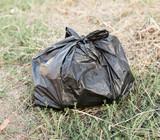 black bag of trash on the ground