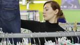 Woman In The Store Choosing Jeans Hanging On Racks