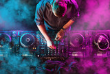 Fototapety Charismatic disc jockey at the turntable. DJ plays on the best, famous CD players at nightclub during party. EDM, party concept.
