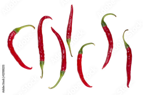 Фигура, выложенная из плодов красного перца на белом фоне - 121188213