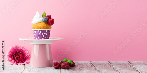 Delicious birthday vanilla cupcake with fresh raspberries, cream and lighted candle on a pink background Poster