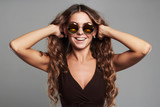 happy smiling beautiful young woman in sunglasses.beauty girl touching healthy hair