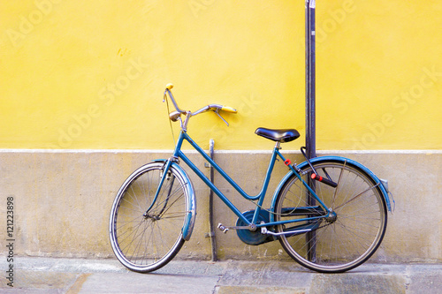 Fotobehang Fiets Blue old bicycle standing near bright yellow wall.