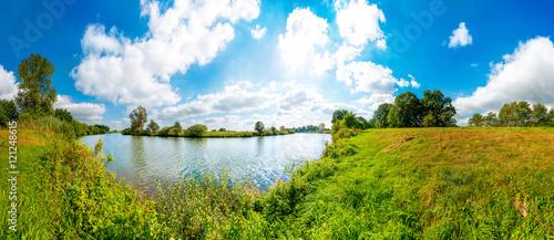 Landschaft mit Fluss, Wiesen, blauen Himmel und Sonne