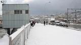 People walking through snow on the bridge. Istanbuls Historical Galata Bridge in winter.