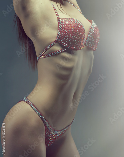 Poster Female bodybuilder with solid defined abs  . fitness bikini