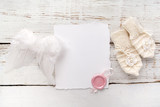Fototapety New Born or baptism Greeting Card. Blank with baby girl gloves and angel wings on white wooden background
