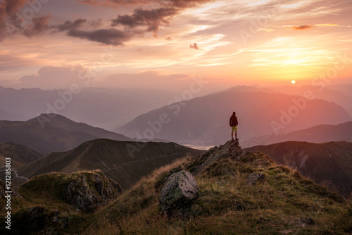 Man standing on a mountain summit at sunset Poster