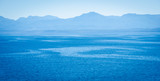 View of ocean streams from a cruise ship with blue skies and mountains in the distance. - 121289674