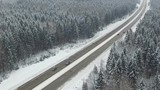 Road in the winter forest with driving cars. Aerial panoramic view. Vanishing point perspective.