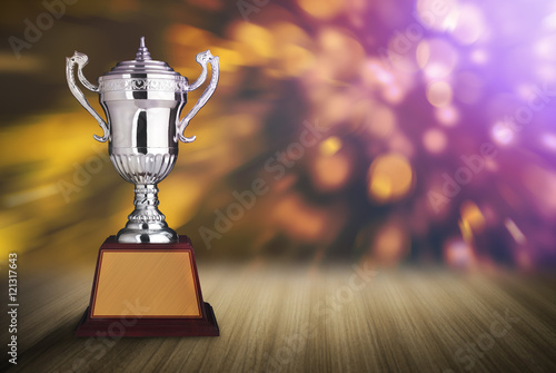 Poster silver trophies on wood table with abstract bokeh lights. defocu