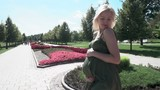 Pregnant blonde girl spinning on the background of the park and sun