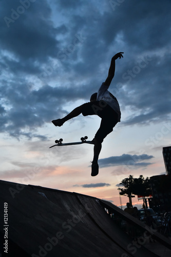 Fotobehang Skateboard Skateboarding as extreme and fun sport. Skateboarder doing a trick in a city skate park.