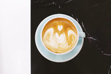 Hot cappuccino or latte coffee on black marble stone table with