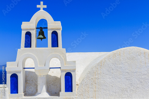 Fotobehang Santorini Arch with a bell, white houses and church with blue domes in Oia or Ia at sunset, island Santorini, Greece