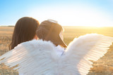 Boy and his mother playing the aviator and look on sunset. The boy in a pilot hat and angel wings sitting on hands of his mother.