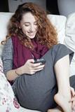 ragazza rannicchiata sul divano sorride con smartphone in mano