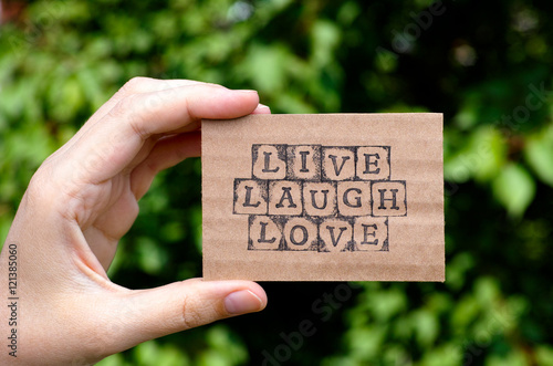 Woman hand holding cardboard card with words Live Laugh Love made by black alphabet stamps opposite green floral background