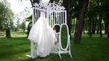 Wedding dress hanging in a beautiful garden.