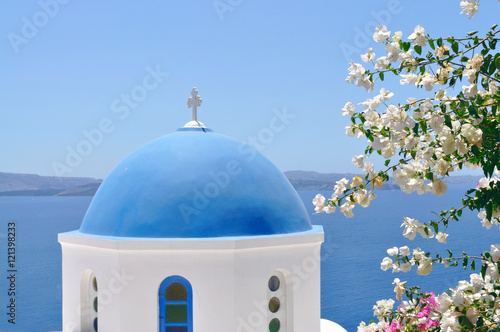 Blue domed church overlooking the Aegean Sea at Oia - Santorini Island in Greece.