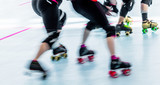 Roller derby skaters action blur. Motion pan shot at rink competition.