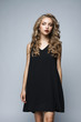 Beautiful girl in a black dress in the studio on a white backgro
