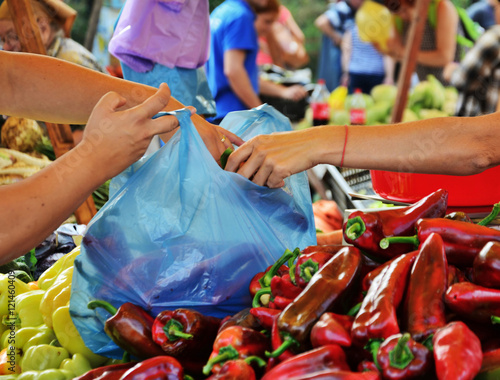 Hands filling a plastic bag with fresh vegetables at the market.