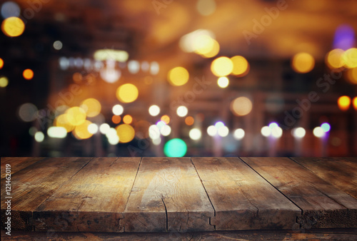 wooden table in front of abstract blurred restaurant lights - 121462019