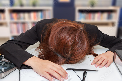 Stressed businesswoman bend down the head at her desk, overwork Poster