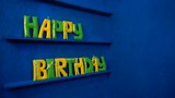 Happy Birthday from felt letters on blue background