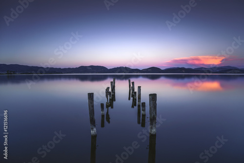 Fotobehang Pier Wooden pier or jetty remains on a blue lake sunset and sky refle