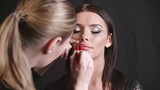 Makeup artist outlining lips of beautiful model with red lip pencil
