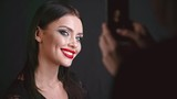 Lady with professional makeup and red lips posing in front of the camera of smart phone and smiling