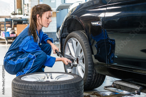 Female Mechanic Changing Car Tire At Automobile Shop