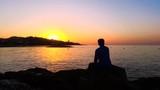 4K - Man sitting among the rocks watching the sunrise