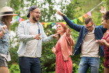happy friends dancing at summer party in garden
