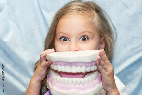 Dentist curing a child patient in the dental office in a pleasant environment. There are specialized equipment to treat all types of dental diseases in the office. - 121580083