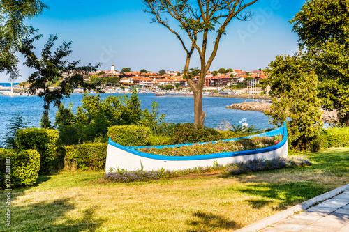 Fotobehang Boat with flowers and old town panorama in Nessebar or Nesebar in Bulgaria, Black sea