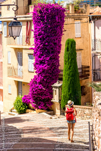 Woman walking near beautiful residential buildings and big flower bush in Cannes city in French riviera. © rh2010