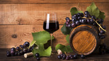 calice di vino rosso con uva e botte