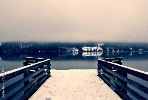 Snow covered wooden jetty on the lake; foggy winter landscape in black and white. Monochrome image filtered in retro, vintage style with soft focus and red filter. Lake Bohinj, Slovenia.