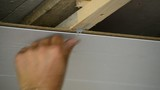 Worker makes the ceiling of MDF panels