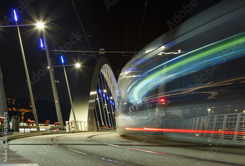Poster Tram speeding over a bridge in Lyon at dusk.
