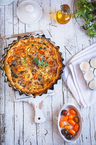 Cheese quiche with cherry tomato and bacon. Top view.