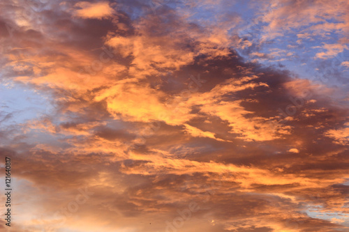 Poster Oranje eclat Fiery sunset with orange cloud and blue sky