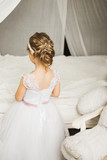 Little bride standing back at the bed in a beautiful dress with
