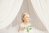 Little bride sitting on the bedl with bouquet